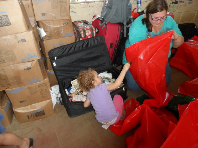 Paige helping Katie pack bags with toys and other prizes to give away.