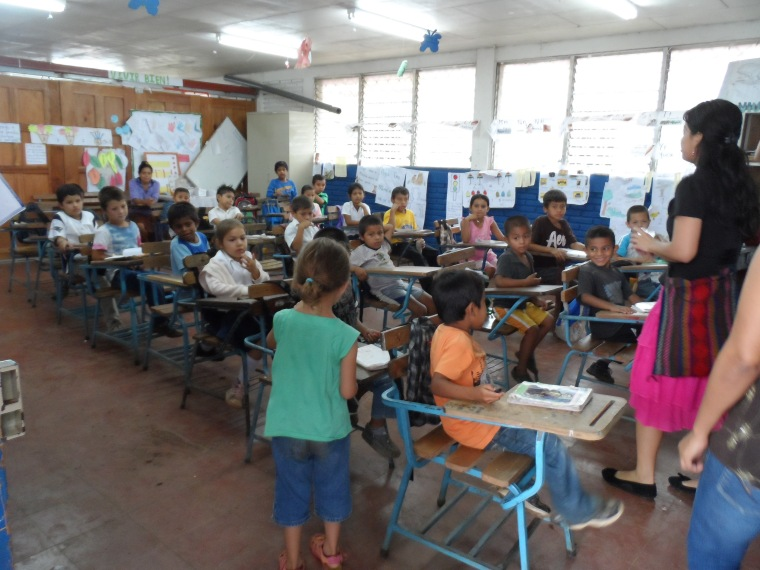 Emma handing out pens in a class.