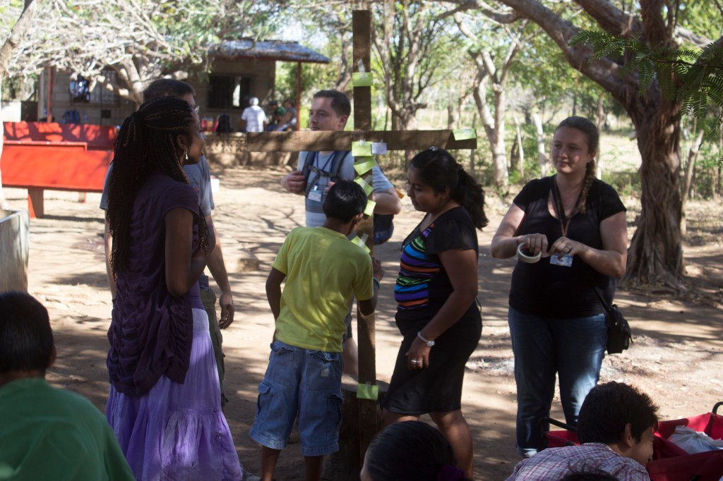 Kids hanging their sins on the cross in the childrens' discipleship program.